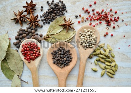 red pepper peas,black pepper peas,white pepper corns,a Bay leaf,cardamom on wooden background