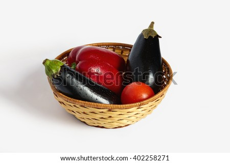 Red pepper, red tomato and two eggplants lie in the wattled plate - stock photo