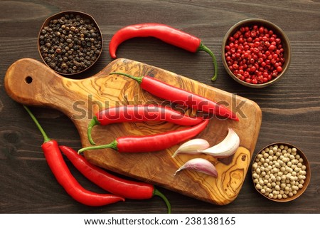 Red peppers and garlic on a wooden kitchen board. - stock photo