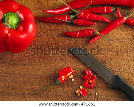Red peppers on wood with knife (up-view)