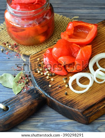 Red peppers pickled in jars with spices and onions on dark wooden background