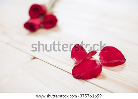 Red petals of roses on wooden board - stock photo
