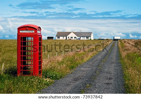 red phone booth standing alone in landscape - stock photo