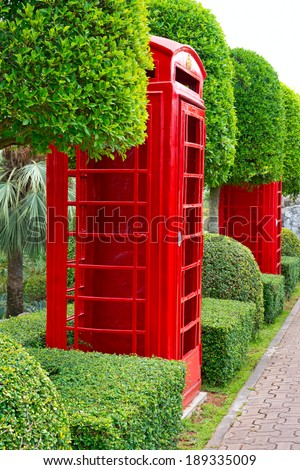 Red phone box in the garden - stock photo