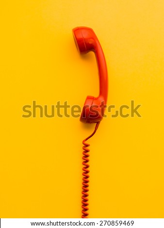 red phone receiver on yellow background - stock photo