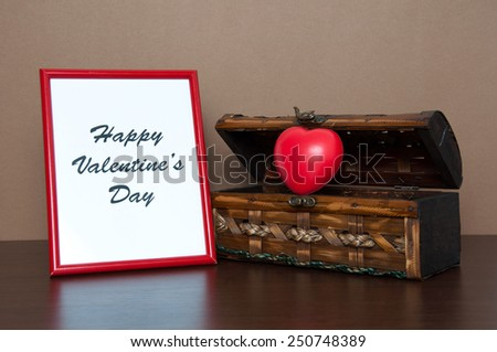Red photo frame and opened decorative chest with heart on wooden table. Valentine day concept. - stock photo
