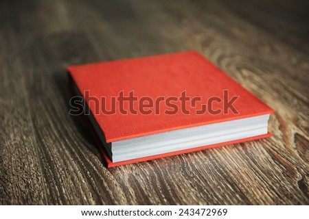 red photobook on wooden table surface - stock photo