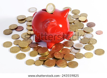 Red piggy bank surrounded by Euro coins with a one euro coin suspended above the slot on a white background in a savings, retirement and investment concept - stock photo