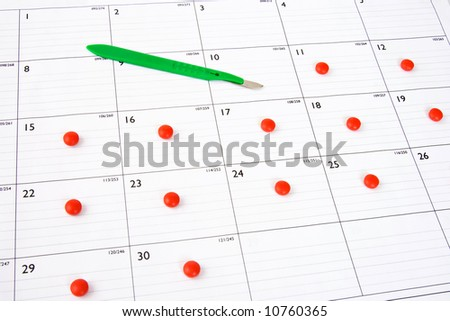 Red pill placed on a calendar daily after scalpel points to a date.