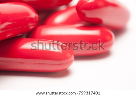 Red pills capsules on white background