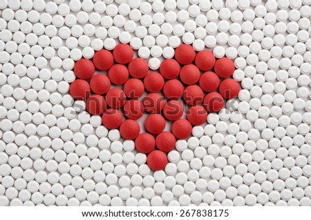 Red pills forming heart symbol - stock photo
