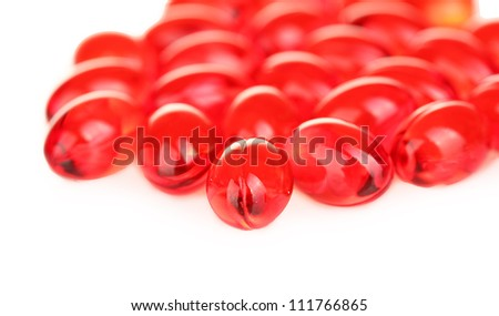 Red pills on white background close-up