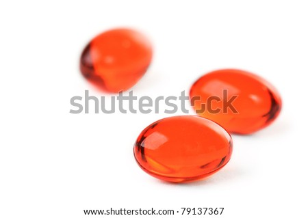 Red pills on white background. Shallow-deep field. Focus on first pill - stock photo