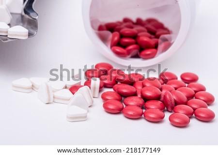 Red pills spilled around a pill bottle - stock photo