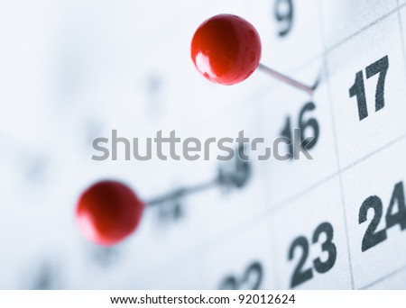 red pin marking date on white calendar - stock photo
