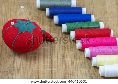 Red pincushion with pins and line of colourful threads on the light wooden background