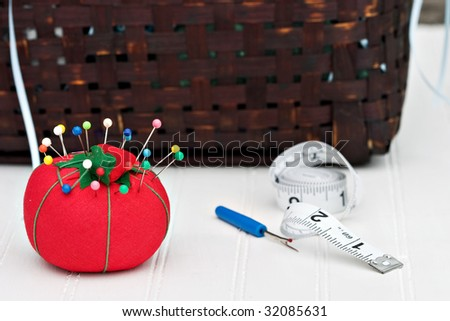 Red pincushion with sewing basket in the background. Shallow DOF. - stock photo