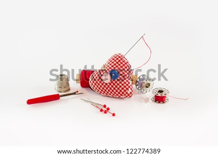 Red pincushion with sewing tools around it - stock photo
