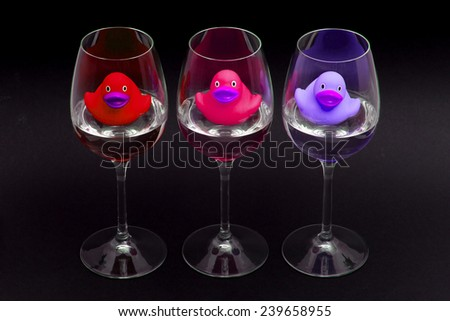 Red, pink and purple rubber ducks in wineglasses, dark background - stock photo