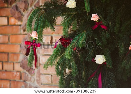 Red & pink roses & ribbons on christmas tree branch - stock photo