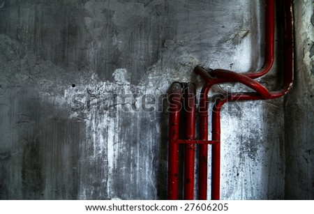 Red pipes on concrete wall spinned and bent forming some sort of sculpture with angel silhuette in background