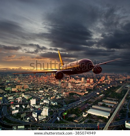 Red plane flying over the city. The sun goes below the horizon, painting the city and the aircraft in fiery sunset colors. - stock photo