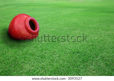 Red planter pot on a field of green grass. - stock photo