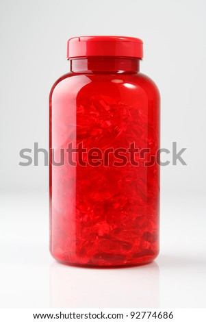 Red Plastic Bottle with Oil Pills on White Background - stock photo