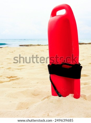Red plastic lifeguard tube on a sandy beach - stock photo
