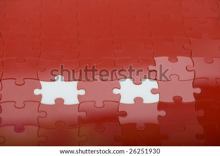 red plastic puzzle with two white pieces - stock photo