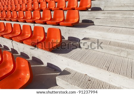 Red plastic seats in a new sunny stadium. - stock photo