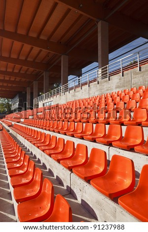 Red plastic seats in a new sunny stadium. Roof made from glue-laminated timber. - stock photo