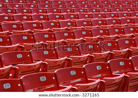 Red plastic seats in rows in an outdoor theatre, front view, numbered