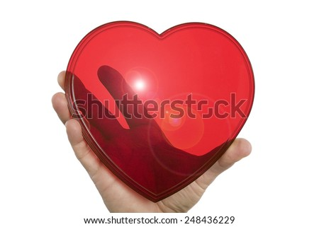 Red plastic transparent heart held up with one hand and isolated on white. - stock photo