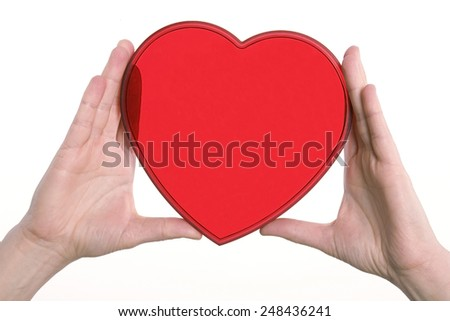 Red plastic transparent heart held up with two hands and isolated on white. - stock photo