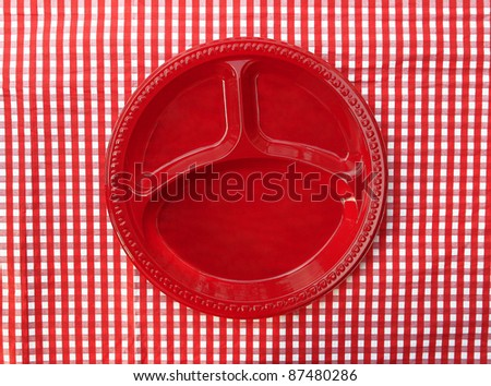 Red Plate Dish with Three Food Compartments isolated on red and white checkered background - stock photo