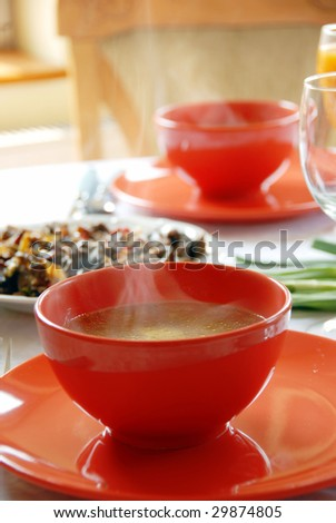 red plates with hot soup served on table in kitchen for dinner - stock photo