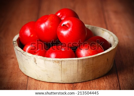 red plums in bowl on wooden table