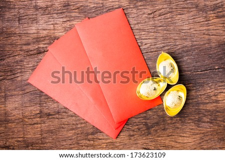 Red pocket and ancient Chinese golden ingots on wooden table top - stock photo