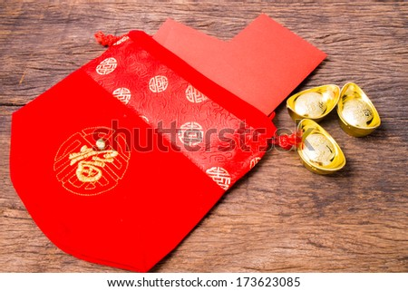 Red pocket in Chinese red bag and ancient Chinese golden ingots on wooden table top - stock photo