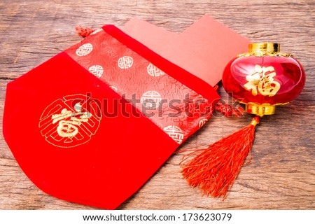 Red pocket in Chinese red bag and Chinese red lantern on wooden table top - stock photo