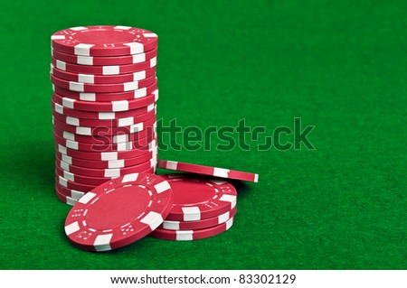red poker chips on a green table background - stock photo