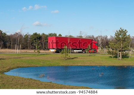 red polish truck waiting for work on an industrial area in the netherlands - stock photo