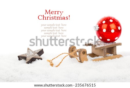 red polka dot Christmas bauble on old rustic wooden sledge over snow, isolated over white background - stock photo