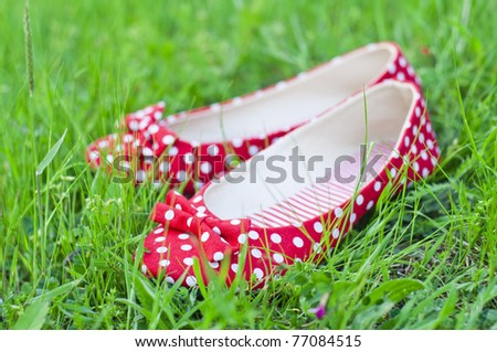 Red polka-dot shoes in a green grass - stock photo