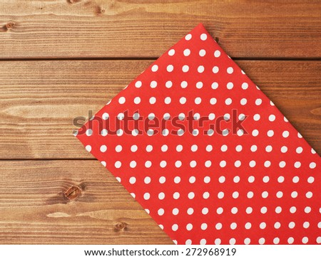 Red polka dot tablecloth or towel over the surface of a brown wooden table - stock photo