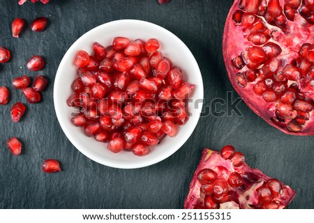 Red pomegranate seeds in a white bowl on table. Open fresh ripe pomegranate. Top view - stock photo