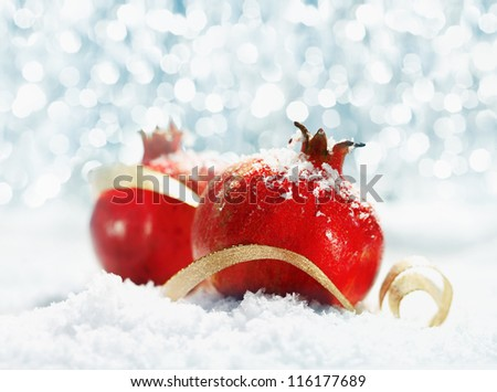 Red pomegranates decorated with a curled gold ribbon and dusted with snow against a sparkling bokeh of Christmas party lights and copyspace for your festive greeting - stock photo
