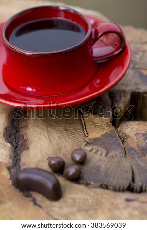 Red porcelain coffee cup, chocolate dragees on chopping block