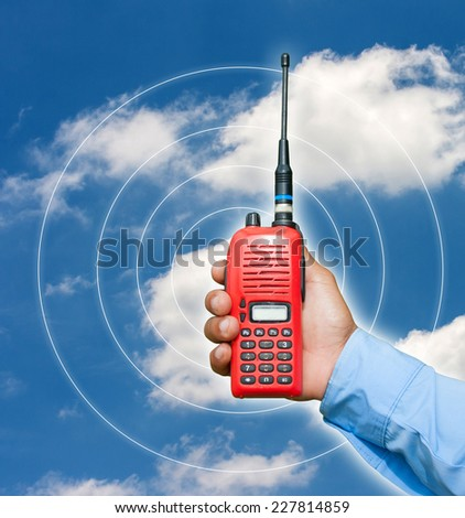 Red portable radio transceiver in hand on blue sky - stock photo